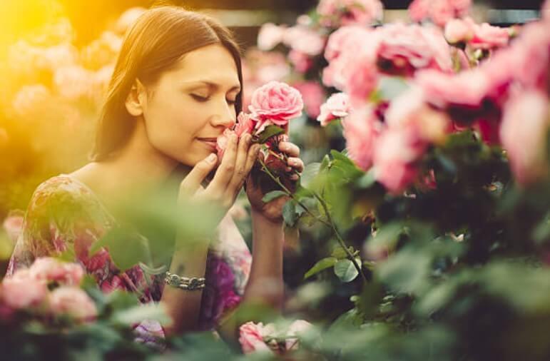 donna che sente l'odore dei fiori